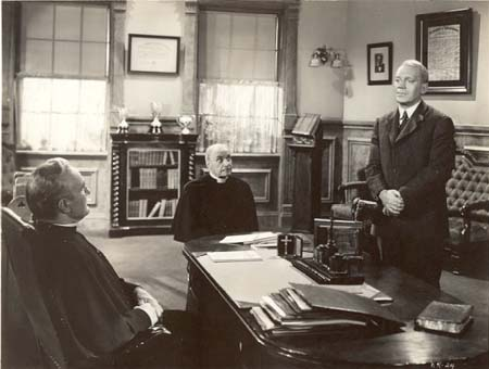 A still from the movie Knute Rockne All American, showing Pat O'Brien (standing) playing Knute as a young chemistry student. His professor was Father Nieuwland, played by German actor Albert Basserman (center). To the left is Donald Crisp who played the mythical university president Father John Callahan.