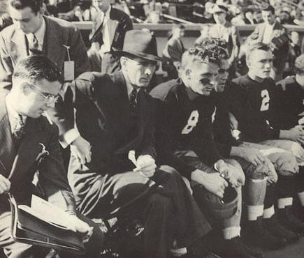 Elmer Layden (hat) is seated on the bench at Notre Dame Stadium. Benny Sheridan (8) sits along side the head coach.